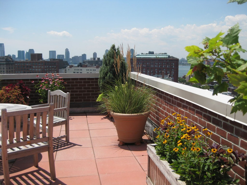 Sheridan Square rooftop deck using concrete pavers with a view overlooking Manhattan.
