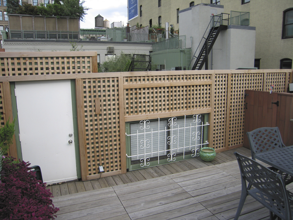 Custom built garden planters and lattice work privacy fence on a rooftop in NYC