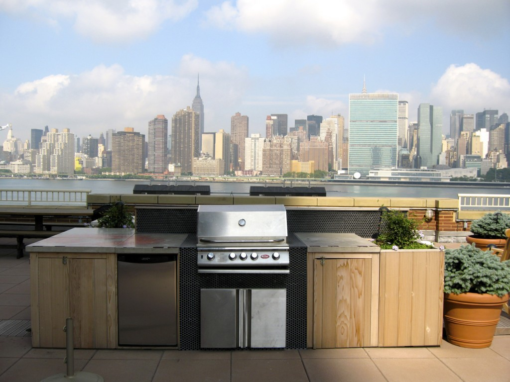 An outdoor kitchen, barbecue and refrigerator on a rooftop deck in Long Island City overlooking Manhattan