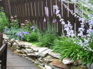 A rock garden retaining wall in a backyard in Brooklyn, NY