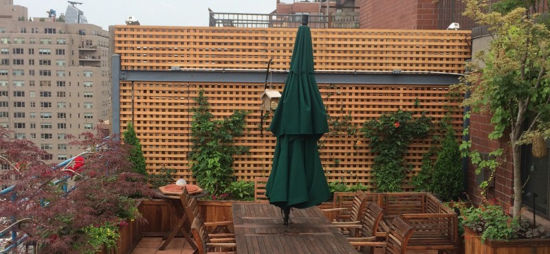 A terrace deck designed by All Decked Out NYC. Wood partition fence, custom planters, pots and garden containers with wooden patio furniture.