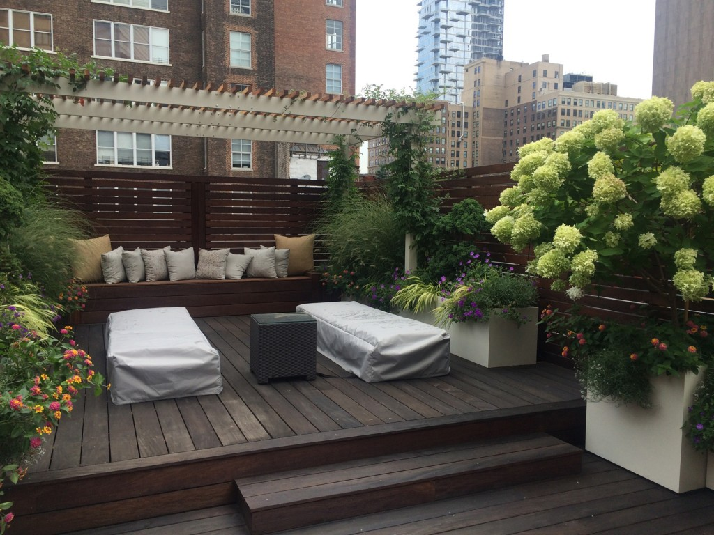 A rooftop deck with patio furniture, with spring flowers in bloom in custom made planters