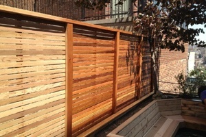 A partially stained fence showing before and after wood stain is painted on the fence